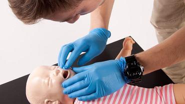 Jeśli zaobserwujesz, że maluch nie może złapać oddechu, blednie, traci przytomność, połóż go na plecach, udrożnij drogi oddechowe, odchylając główkę do tyłu, jeśli widzisz ciało obce, spróbuj je wyjąć palcami.
