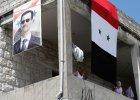 Flaga Syrii i plakat prezydenta Al-Assada