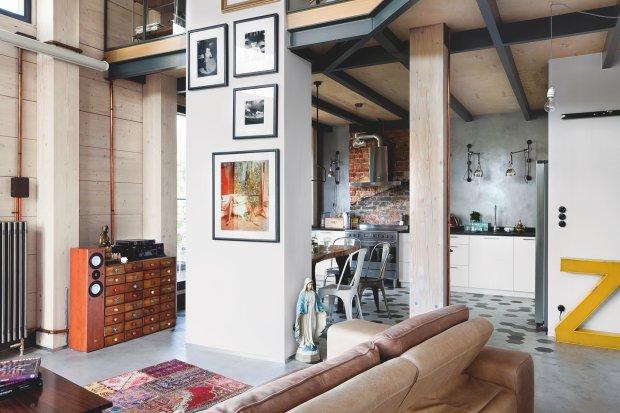 Przestrzeń salonu łączy się z kuchnią. Za okapem stary komin z odkrytą przedwojenną cegłą. Podkreśla nieco