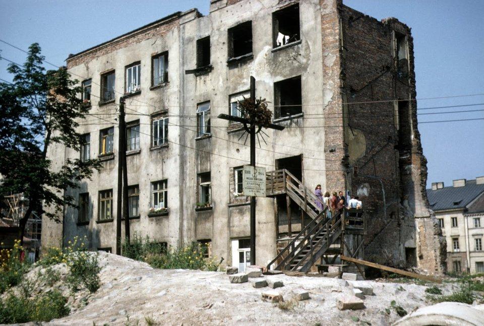 Jeden z domów, który - choć zrujnowany - przetrwał wojnę. Na pierwszym planie krzyż z symbolem Polski Walczącej