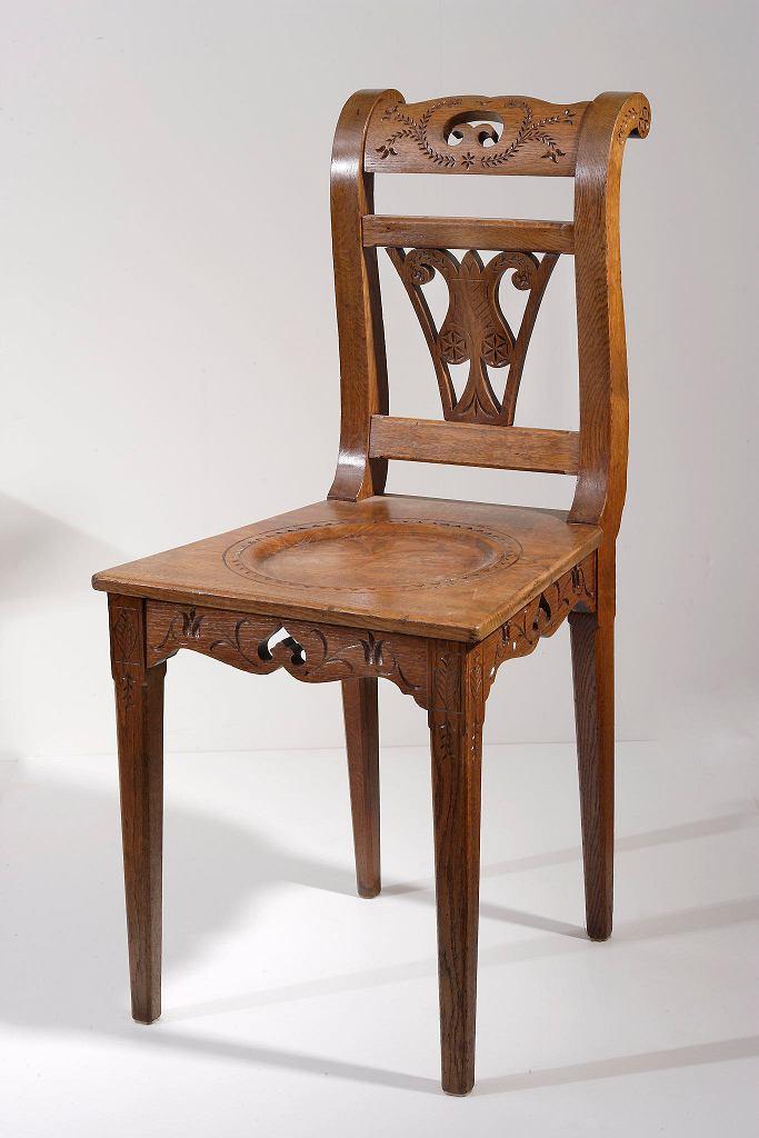 Krzesło w stylu zakopiańskim 1903-1911, dębowe, rytowane, z deskowym, trapezoidalnym siedzeniem i ażurowym oparciem z motywem stylizowanego kwiatu.  / LIGIER PIOTR