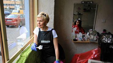 Elżbieta Jurek w oknie swojego salonu fryzjerskiego