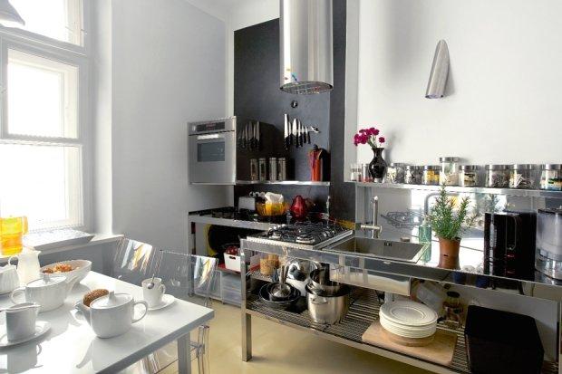 Otwarta stalowa zabudowa kuchenna - projekt Agaty.  Polerowany metal odbija �wiat�o i powi�ksza optycznie przestrze� niedu�ej kuchni. Nad zlewem minimalistyczna lampa ogrodowa.