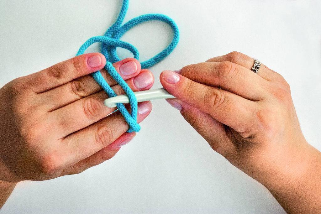 Bawełniany sznurek (gr. 10 mm) okręcamy dwa razy wokół trzech palców. Wsuwamy szydełko (śr. 10 mm) pomiędzy sznurki, zahaczając ten ułożony głębiej na dłoni, i przeciągamy go pod drugim.