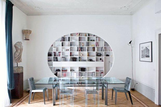 Kadr doskonały. Prosta?biała biblioteka, zaprojektowana przez?panią domu, w obramowaniu owalu?ściany.