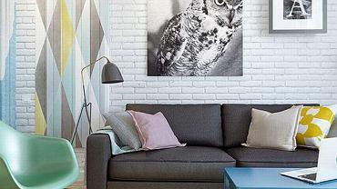 Ceglaną ścianę w salonie pomalowano na biało, wprowadzając tym samym industrialny akcent. Na jej tle dobrze się prezentuje klasyczna, szara sofa. Pastelowe meble i dekoracje ożywiają wnętrze.