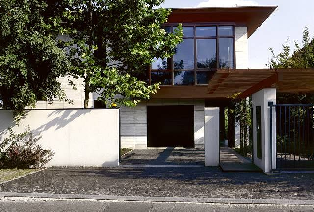 Widok na dom od strony ulicy. Za przeszklonymi ścianami na piętrze zaplanowano pracownię plastyczną. Drugi podobny szklany kubik od strony skarpy mieści jadalnię