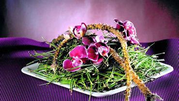 1. Stroik DANIE NA OSTRO Na ceramicznym talerzu usypano gęsty kopczyk z sosnowych igieł. Ukryto w nim plastikowe fiolki, w których umieszczono pędy storczyka falenopsis. Na wierzchu ułożono nagie gałązki sosny.