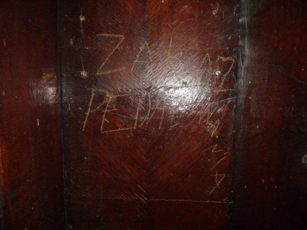Wyryty na drewnianych drzwiach napis ''Zakaz pedałowania''