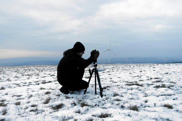 Astronom przygotowuje aparat do zmierzenia poziomu światła emitowanego przez szklarnię