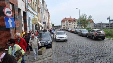 Wycieczka niemieckich turystów przedziera się przez zastawione autami chodniki na ul. Panieńskiej