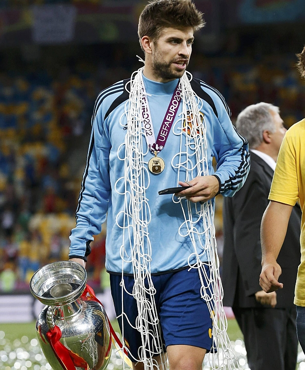 Spain's Gerard Pique walks with the trophy and a net he cut after defeating Italy to win the Euro 2012 final soccer match at the Olympic stadium in Kiev, July 1, 2012.                REUTERS/Alessandro Bianchi (UKRAINE  - Tags: SPORT SOCCER)