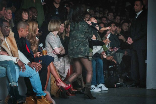 _Kim Kardashian gets up to carry her daughter, North, backstage as she walks near Sean Combs (L), Jay-Z (2nd L), Beyonce (3rd L) and Anna Wintour (4th L) during a presentation of Kanye Wests Fall/Winter 2015 partnership with Adidas at New York Fashion Week February 12, 2015. REUTERS/Lucas Jackson (UNITED STATES - Tags: FASHION SOCIETY ENTERTAINMENT)