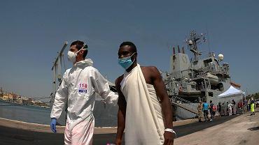 Port w Brindisi 30 czerwca: jeden z 402 migrantów wysadzonych przez okręt brytyjskiej marynarki, któremu pomocy udziela sanitariusz