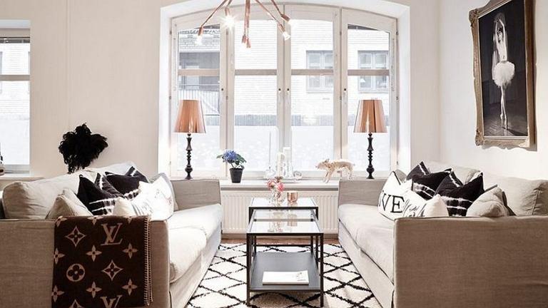 Część wypoczynkowa. Kanapy obite naturalnym lnem, czarno białe poduszki i miedziane dodatki.