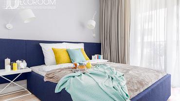 W sypialni szczególną uwagę zwraca duże łóżko z zagłówkiem wykonanym z miękkiej tkaniny w kolorze granatowym