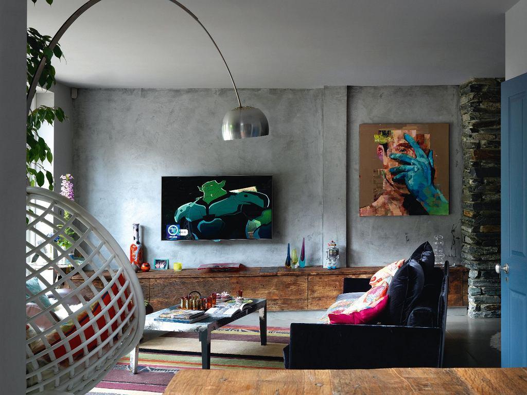 W salonie szorstkość betonu łagodzą barwne plamy obrazów. Po prawej portret z kolekcji The Acquaintance kanadyjskiego artysty Andrew Salgado. Na pierwszym planie rattanowy bujak Kata (Conran Contracts).