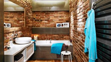 ŁAZIENKA. Wnętrze oświetlają sufitowe halogeny oraz taśmy LED zainstalowane za załomem podwieszonego sufitu, pod półką i w cokole wanny. Te dwa ostatnie punkty świetlne znakomicie kreują relaksujący klimat. Drewniana rama dużego lustra, dopasowana kolorem do ceglanej ściany, idealnie się w nią wtapia.