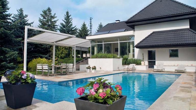 Basen w ogrodzie. Ulubione miejsce domowników w upalne dni. Wokół basenu okładzina z łupka brazylijskiego, na dachu domu baterie słoneczne podgrzewające wodę w basenie