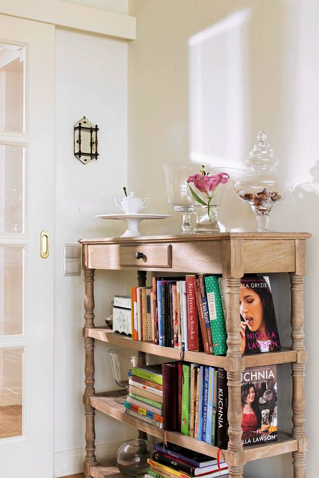 Ozdobna etażerka na nogach z tralek z powodzeniem służy jako biblioteczka. na jej szczycie ustawiono dekoracyjne szklane naczynia. Delikatne formy stanowią idealne uzupełnienie kompozycji.