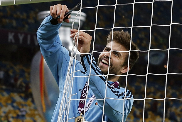 Spain's Gerard Pique cuts the net after  the Euro 2012 soccer championship final  between Spain and Italy in Kiev, Ukraine, Monday, July 2, 2012. (AP Photo/Gregorio Borgia)