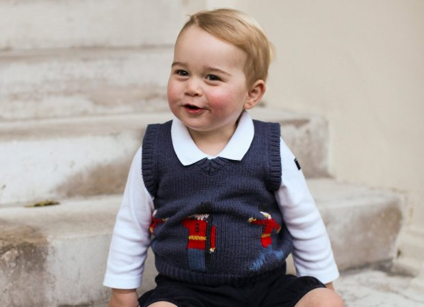 FILE -This is a file image taken in late Nov. 2014  and provided by The Duke and Duchess of Cambridge of Britain's Prince George as he poses for a photograph in a courtyard at Kensington Palace, London. Parents looking to dress their toddlers like Prince George for Christmas may be too late. The royal toddler was seen wearing a blue sweater decorated with soldiers of a Guards regiment in bearskin hats and red tunics in official holiday pictures released last weekend.  (AP Photo/TRH The Duke and Duchess of Cambridge) NO SALES, EDITORIAL USE ONLY