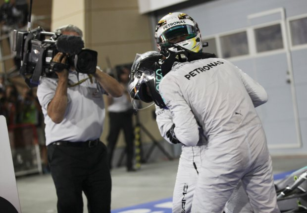 Winner Mercedes driver Lewis Hamilton of Britain, top, jokes fighting with his teammate second placed Mercedes driver Nico Rosberg of Germany after the Bahrain Formula One Grand Prix at the Bahrain International Circuit in Sakhir, Bahrain, Sunday, April 6, 2014. (AP Photo/Hasan Jamali)