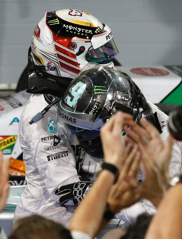 Mercedes driver Lewis Hamilton of Britain, winner, up left, celebrates with his teammate the second placed Mercedes driver Nico Rosberg of Germany after winning the Bahrain Formula One Grand Prix at the Formula One Bahrain International Circuit in Sakhir, Bahrain, Sunday, April 6, 2014. (AP Photo/Hassan Ammar)