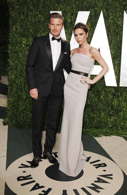 Soccer player David Beckham and his wife, singer Victoria Beckham, pose as they arrive at the 2012 Vanity Fair Oscar party in West Hollywood, California February 26, 2012.  REUTERS/Danny Moloshok (UNITED STATES - Tags: ENTERTAINMENT SPORT SOCCER)