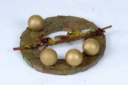 P�aski kr��ek, np. ze styropianu, oklejono preparowanymi li��mi kokoloby. Asymetryczne u�o�enie �wiec, kt�re przyklejono, rozdzielaj� pa�eczki cynamonu.