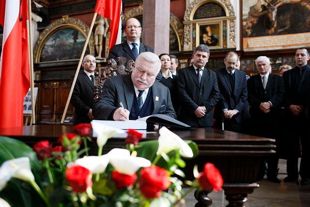 Lech Wałęsa wpisuje się do księgi kondolencyjnej.