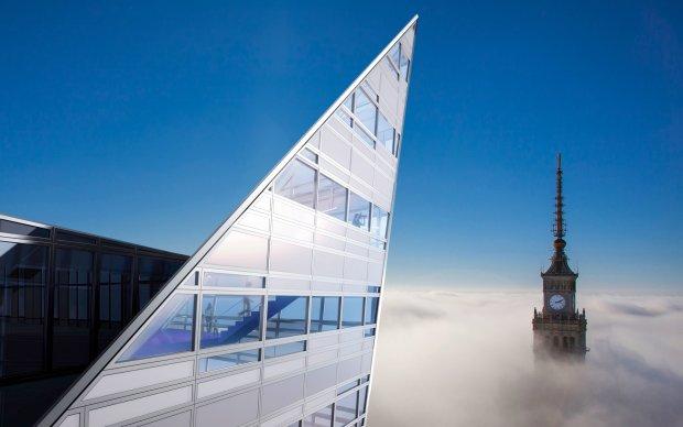 Warszawa przykryta chmurami. Ponad nimi wy��cznie fragmenty najwy�szych budynk�w. Widok z ostatnich pi�ter apartamentowca Z�ota 44 na zegar na szczycie Pa�acu Kultury jest absolutnie wyj�tkowy.