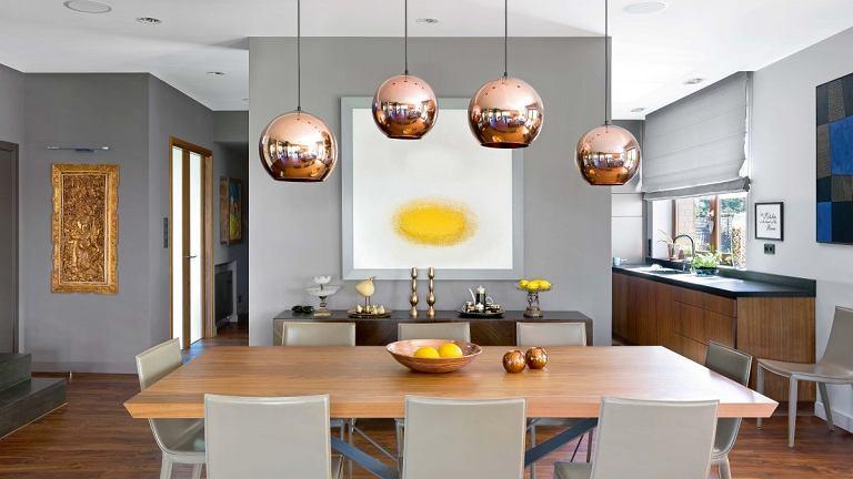 Masywny drewniany blat stołu Skorpio Wood, Cattelan Italia, opiera się na rozrzeźbionych stalowych nogach. Krzesła Cattelan Italia, lampy Copper, Tom Dixon.