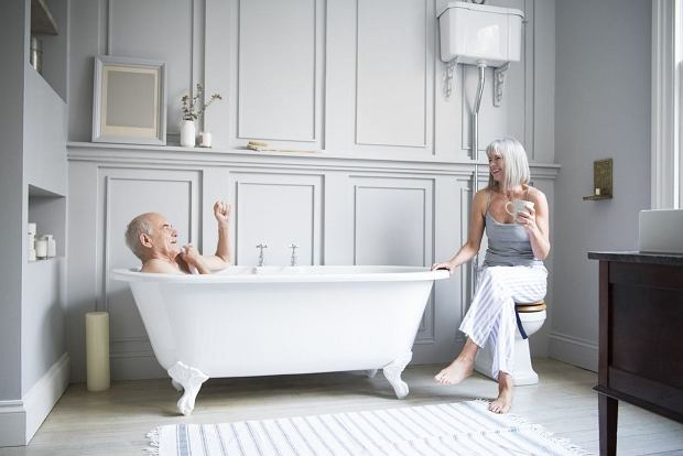 Senior couple in hotel bathroom. Man is taking a bath and woman is sitting with a coffee. They are having a relaxed conversation and are smiling and happy.