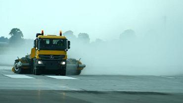 Specjalne ciężarówki ze szczotkami jadą parami, czyszcząc powierzchnię drogi startowej
