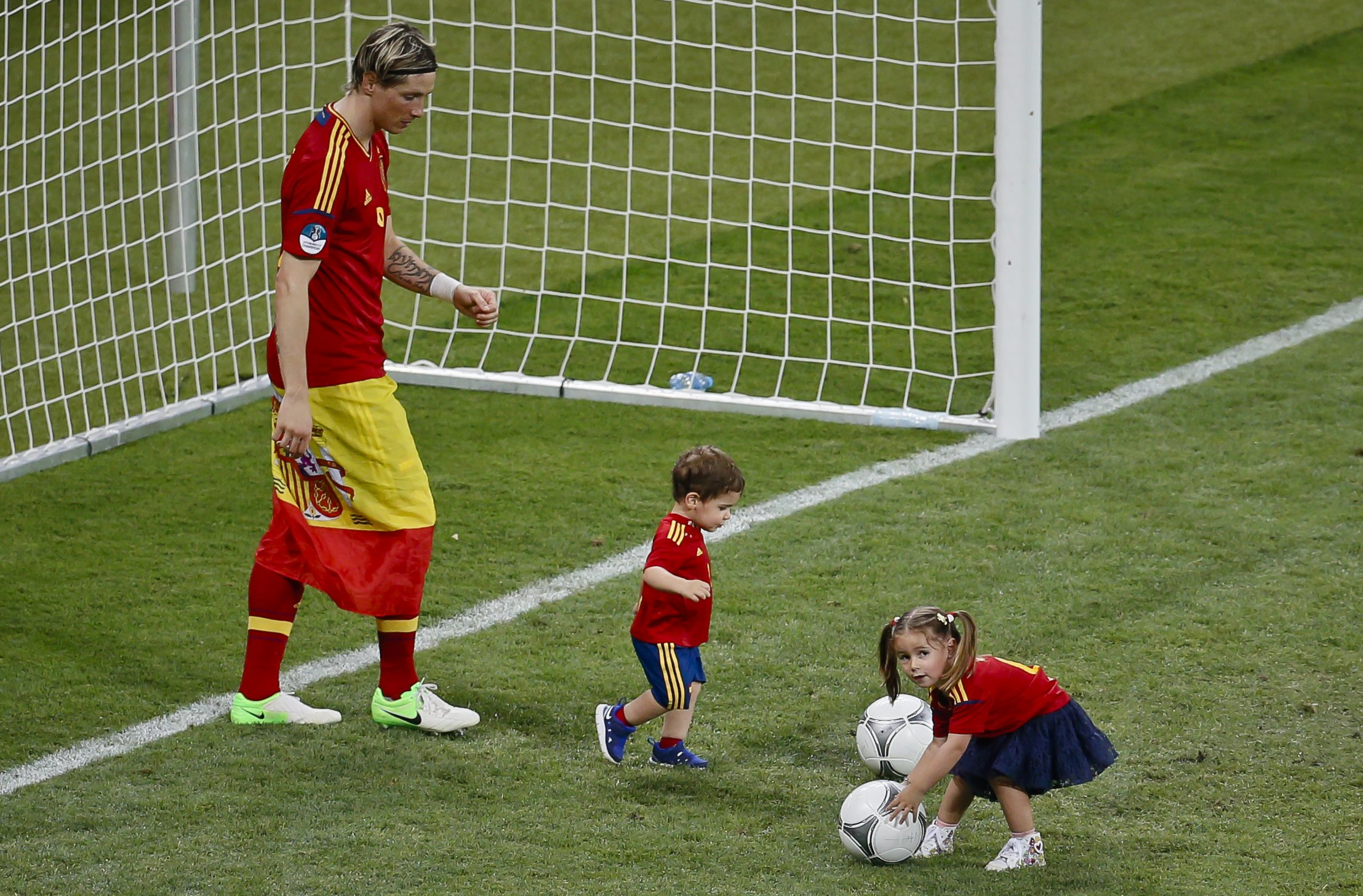 Spain's Fernando Torres, left, plays with his son Leo, center, and daughter Nora, right, after an award ceremony as Spain won the Euro 2012 soccer championship final between Spain and Italy in Kiev, Ukraine, early Monday, July 2, 2012. (AP Photo/Vadim Ghirda)