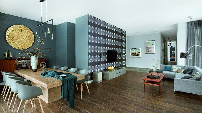 Ścianę z telewizorem zdobi tapeta (Elitis) przypominająca batik. Krzesła All About Chair (HAY), obrus NAP, stolik kawowy vinatge upolowany na Allegro. Na ścianie w głębi grafiki Lecha Batora.