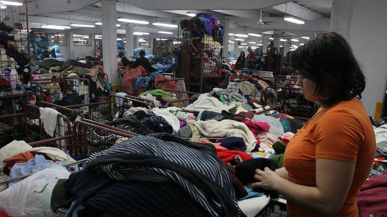 Kobieta przy pracy w sortowni odzieży używanej