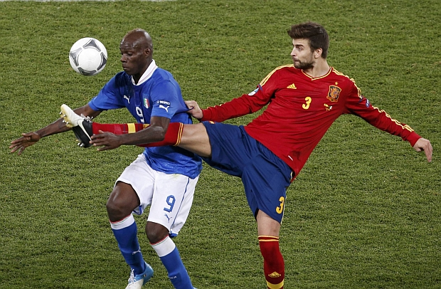 Spain's Gerard Pique (R) battles for the ball with Italy's Mario Balotelli during their Euro 2012 final soccer match at the Olympic Stadium in Kiev July 1, 2012.  REUTERS/Charles Platiau (UKRAINE  - Tags: SPORT SOCCER)