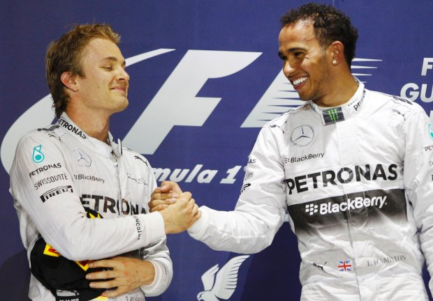 Mercedes Formula One driver Lewis Hamilton of Britain (R) is congratulated by teammate Mercedes Formula One driver Nico Rosberg of Germany on the podium after he won the Bahrain F1 Grand Prix at the Bahrain International Circuit (BIC) in Sakhir, south of Manama April 6, 2014. REUTERS/Thaier Al-Sudani (BAHRAIN  - Tags: SPORT MOTORSPORT F1)