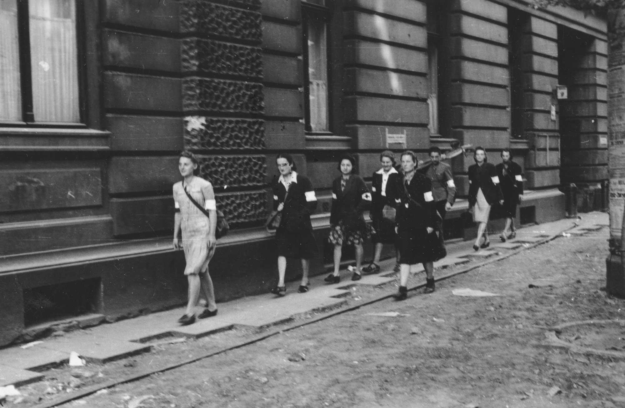 Wymarsz patrolu sanitarnego Wojskowej Służby Kobiet AK na ulicy Moniuszki 9, 5 sierpnia 1944 (fot. Eugeniusz Lokajski / Wikimedia.org / http://bit.ly/1DaYdPq)