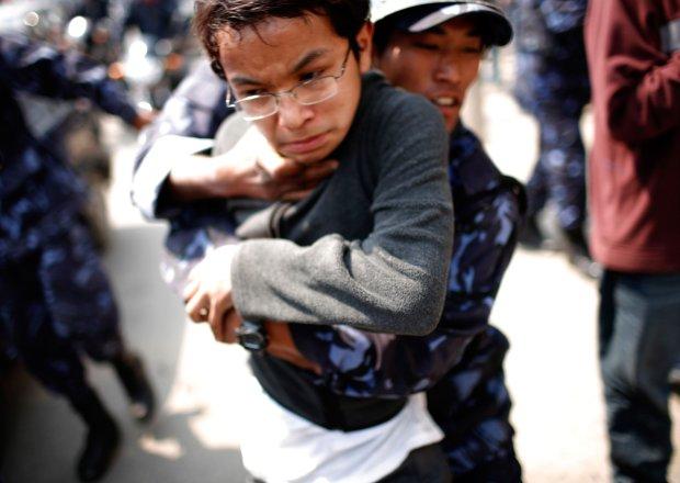 Nepalski policjant zatrzymuje studenta podczas demonstracji w Katmandu