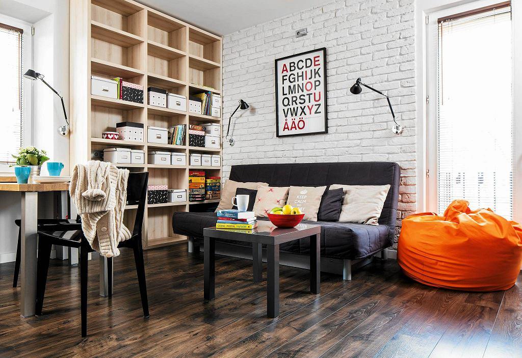 Funkcjonalnie i stylowo. Lekka kanapa z funkcją spania nie zajmuje dużo przestrzeni. Drewniany regał na całą ścianę zapewnia miejsce na przechowywanie.