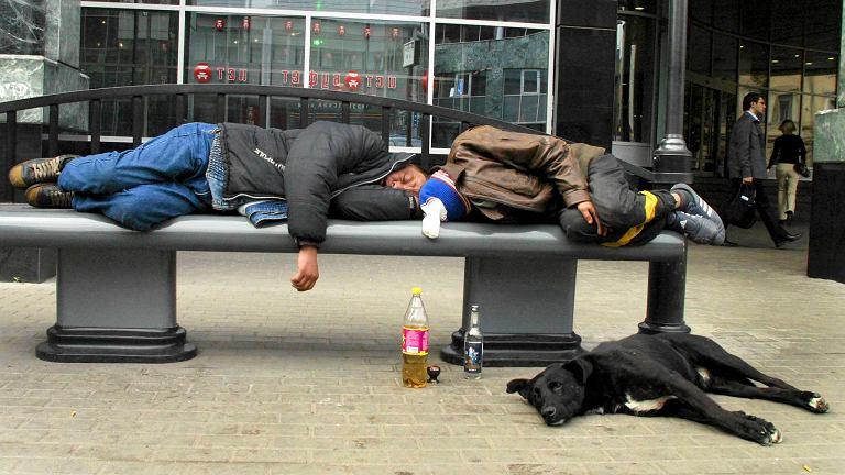 Mężczyźni śpiący na ławce w Moskwie