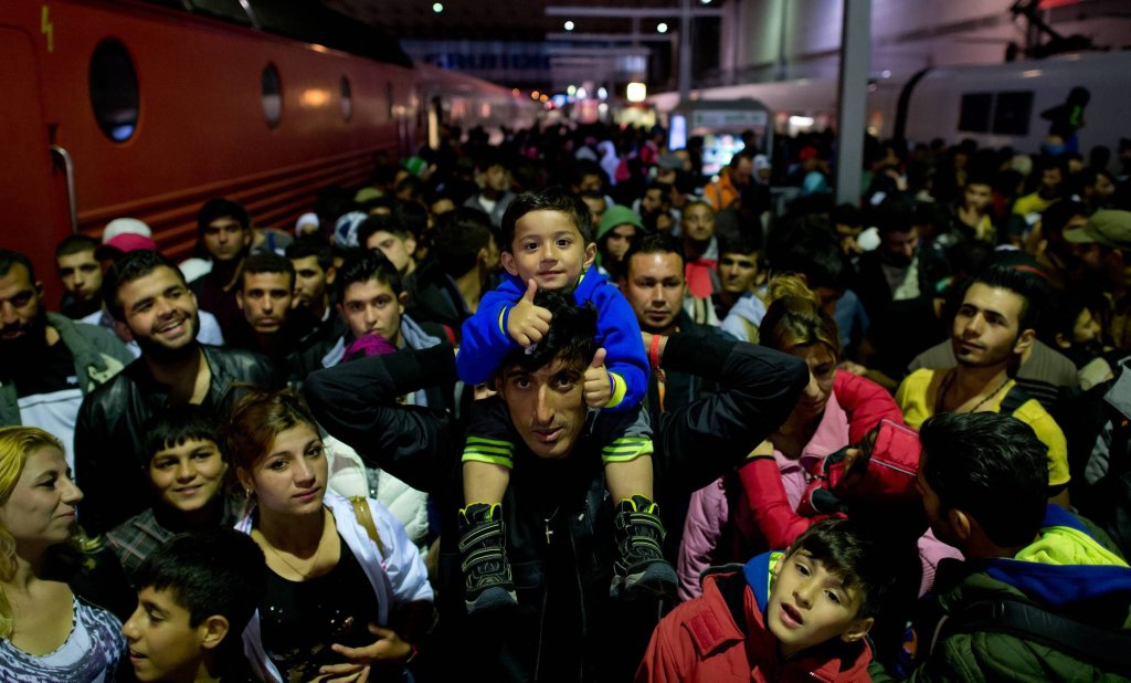 In this Sunday, Sept. 6, 2015 photo refugees, children, women, men, who have arrived by train from Salzburg, Austria, wait on a platform at the central station in Munich, Germany. More than 10000 migrants have arrived in Germany over the past weekend. (Sven Hoppe/dpa via AP) SLOWA KLUCZOWE: migration;#migration;refugee;social issues;asylum;train station;platform;waiting