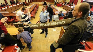 """Działacze stowarzyszenia """"Miasto Jest Nasze"""" przynieśli na sesję drewniane koryto dla Platformy"""
