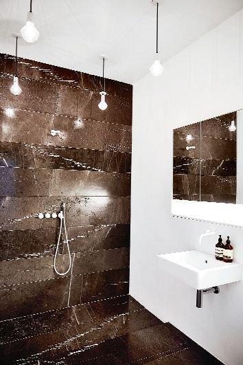 W łazience irański marmur w kolorze gorzkiej czekolady zestawiono z bielą ścian i urządzeń sanitarnych ? prosty pomysł, szlachetny materiał, wyrafinowany efekt. Armatura pochodzi z duńskiej firmy Vola Decorum.