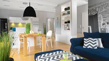 Pokój dzienny, kuchnia i przedpokój tworzą otwartą przestrzeń z wyraźnie wyodrębnionymi strefami o różnej funkcji. Kuchenna zabudowa dyskretnie wtapia się w tło, nie dominując nad częścią wypoczynkową.
