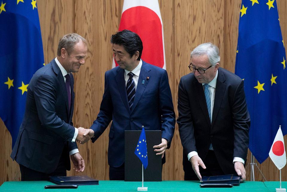 Premier Shinzo Abe ściska dłoń przewodniczącego Rady Europejskiej Donalda Tuska tuż po podpisaniu umowy handlowej Japonia-UE, obok stoi szef Komisji Europejskiej Jean-Claude Junker. Tokijska siedziba rządu, 17 lipca 2018 r.