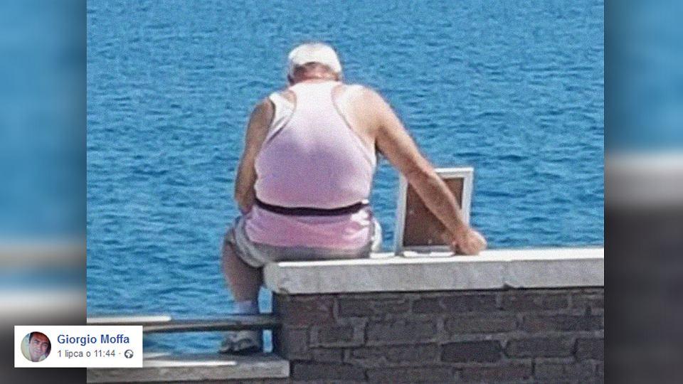 Samotny staruszek siedzi w porcie.